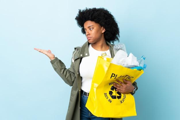 의심과 다채로운 지주 copyspace에 고립 된 재활용 가방을 들고 젊은 아프리카 계 미국인 여자