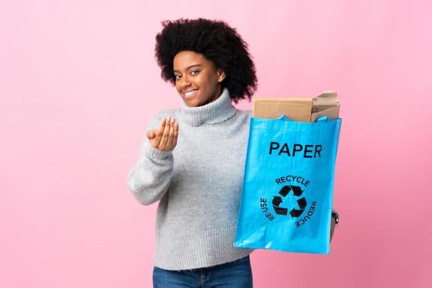 Молодая афро-американская женщина держа сумку рециркулировать изолированную на красочном приглашать прийти с рукой. счастлив, что ты пришел