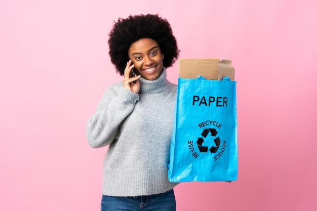 Молодая афроамериканская женщина, держащая рециркуляционную сумку, изолированная на красочной стене, поддерживающая разговор с мобильным телефоном с кем-то