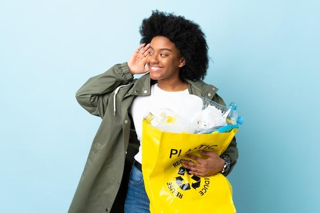 Молодая афроамериканец женщина, держащая рециркуляции мешок, изолированные на красочные стены, слушая что-то, положив руку на ухо