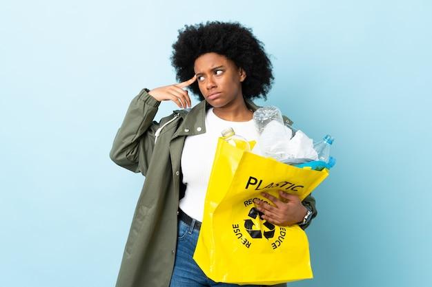 頭に指を入れて狂気のジェスチャーを作るリサイクルバッグを保持している若いアフリカ系アメリカ人女性