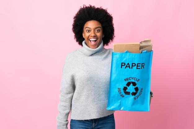 驚きの表情でリサイクルバッグを保持している若いアフリカ系アメリカ人女性