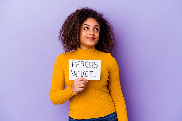 難民を保持している若いアフリカ系アメリカ人の女性は、目標と目的を達成することを夢見て孤立したプラカードを歓迎します