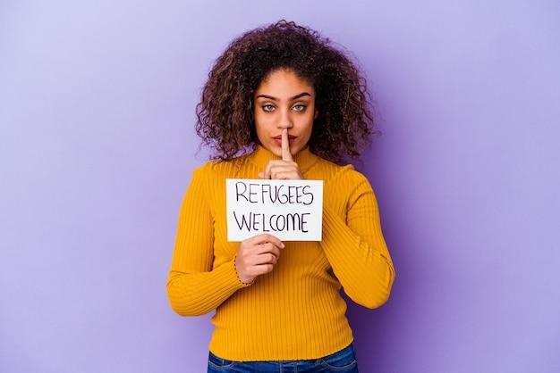 난민 환영 현수막을 들고 젊은 아프리카 계 미국인 여자는 비밀을 유지하거나 침묵을 요구하는 격리.