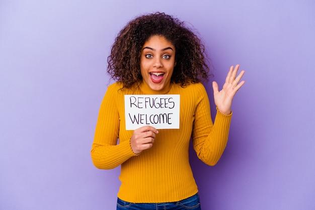 고립 된 난민 환영 현수막을 들고 젊은 아프리카 계 미국인 여자