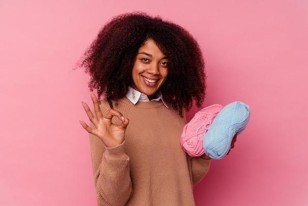 쾌활하고 자신감이 확인 제스처를 보여주는 분홍색 배경에 고립 된 바느질 스레드를 들고 젊은 아프리카 계 미국인 여자.