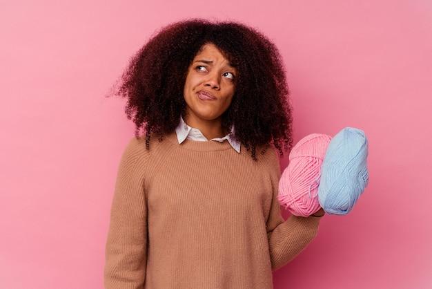 ピンクの背景にミシン糸を持った若いアフリカ系アメリカ人女性は、混乱し、疑わしく、確信が持てません。