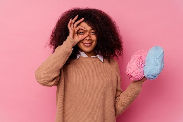 분홍색 배경에 고립 된 바느질 스레드를 들고 젊은 아프리카 계 미국인 여자는 눈에 확인 제스처를 유지 흥분.