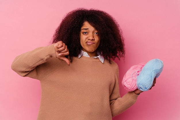 ピンクの背景にミシン糸を持った若いアフリカ系アメリカ人女性が、嫌いなジェスチャーを示し、親指を下に向ける。不一致の概念。