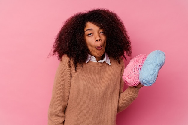 ピンクの背景に縫い糸を持った若いアフリカ系アメリカ人女性が肩をすくめ、混乱して目を開けている。