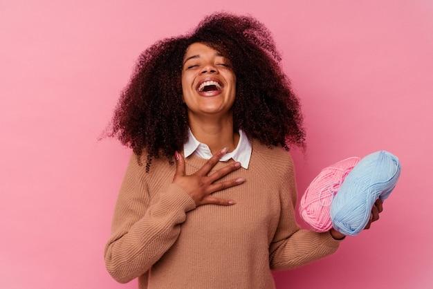 Молодая афро-американская женщина, держащая швейные нитки, изолированные на розовом, громко смеется, держа руку на груди.