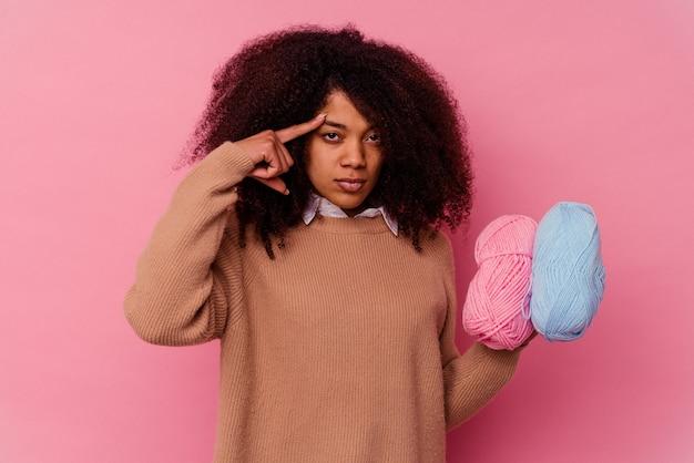 생각, 작업에 초점을 맞춘 손가락으로 사원을 가리키는 핑크에 고립 된 바느질 스레드를 들고 젊은 아프리카 계 미국인 여자.