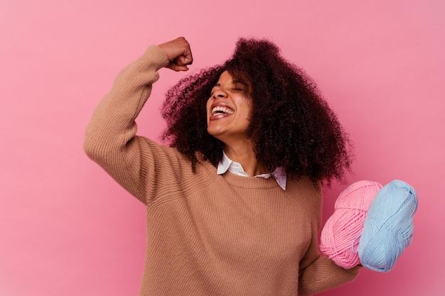 승리, 승자 개념 후 주먹을 올리는 핑크에 고립 된 바느질 스레드를 들고 젊은 아프리카 계 미국인 여자.