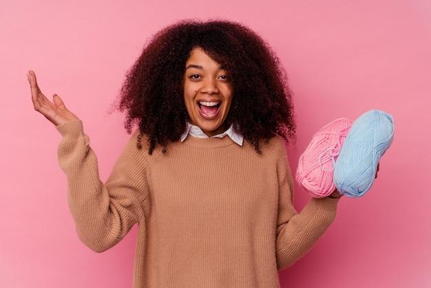 즐거운 놀라움을 받고, 흥분하고 손을 올리는 분홍색에 고립 된 바느질 스레드를 들고 젊은 아프리카 계 미국인 여자.