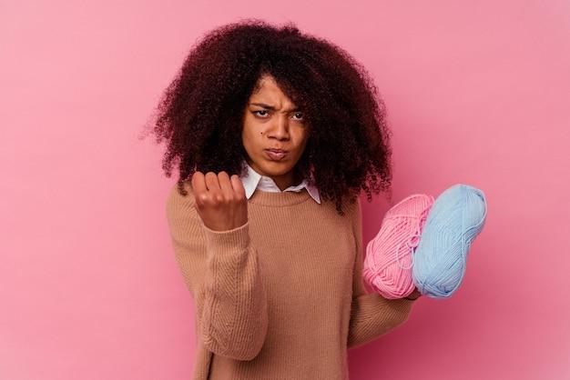 주먹, 공격적인 표정을 보여주는 분홍색에 고립 된 바느질 스레드를 들고 젊은 아프리카 계 미국인 여자.
