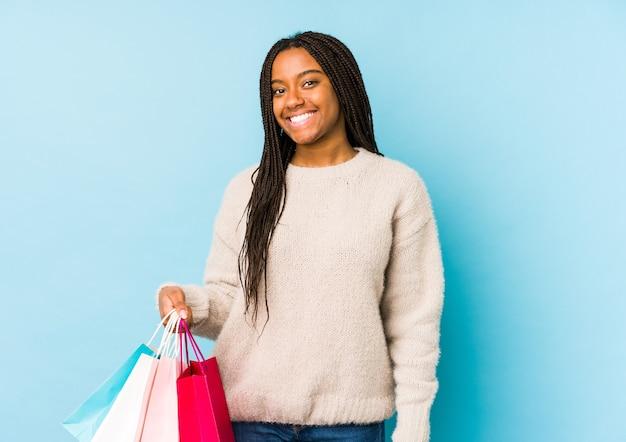 ショッピングバッグを保持している若いアフリカ系アメリカ人女性は幸せ、笑顔、陽気を分離しました。