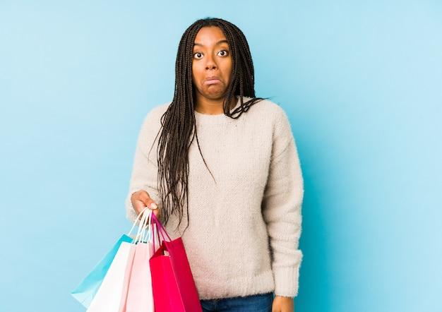 Молодая афро-американская женщина, держащая изолированную сумку для покупок, пожимает плечами и смущает открытые глаза.
