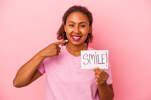분홍색 배경에 격리된 미소 플래카드를 들고 있는 젊은 아프리카계 미국인 여성