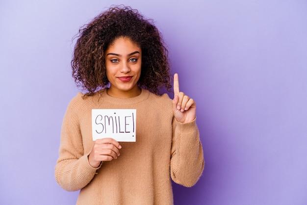 Молодая афро-американская женщина, держащая плакат улыбки, изолированные на фиолетовой стене, показывая номер один пальцем.