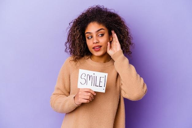 Молодая афроамериканская женщина, держащая плакат улыбки, изолированная на фиолетовой стене, пытается слушать сплетни