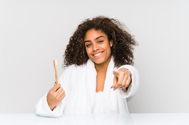 正面を向いて歯ブラシの陽気な笑顔を持っている若いアフリカ系アメリカ人女性。