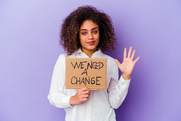 젊은 아프리카 계 미국인 여자를 들고 우리는 보라색 배경에 고립 된 변경 현수막이 필요 손가락으로 5 번 명랑 게재 웃 고.