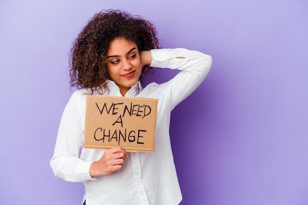 Молодая афро-американская женщина, держащая табличку с надписью «нам нужно изменить», изолированную на фиолетовом фоне, касаясь затылка, думая и делая выбор.