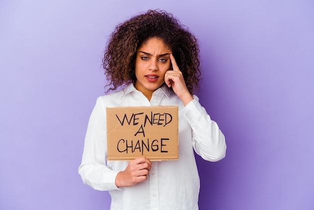 Молодая афро-американская женщина, держащая табличку с надписью «нам нужен», изолированной на фиолетовой стене, показывая жест разочарования указательным пальцем.