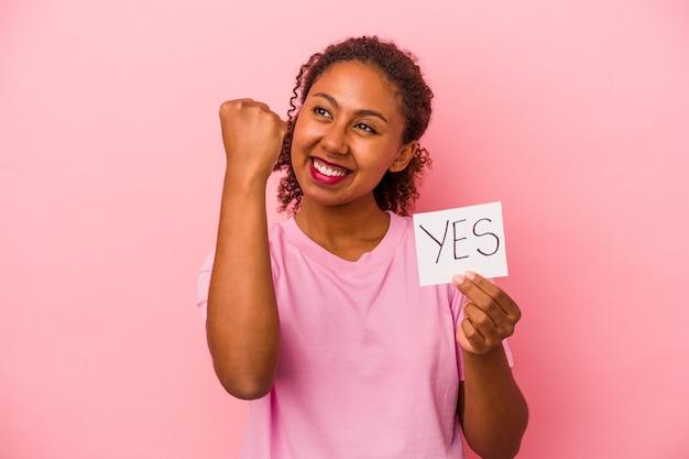 ピンクの背景で隔離のはいプラカードを保持している若いアフリカ系アメリカ人女性