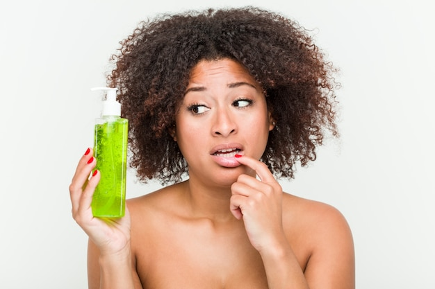 Young african american woman holding aloe vera bottle relaxed thinking about something looking at a copy space.