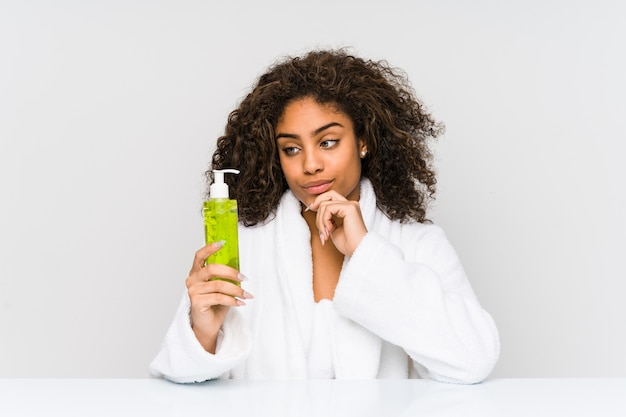 Young african american woman holding an aloe vera looking sideways with doubtful and skeptical expression.