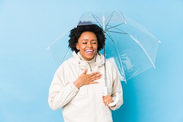 分離された傘を保持している若いアフリカ系アメリカ人女性は大声で胸に手を置いて笑います。