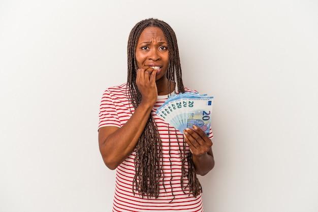 若いアフリカ系アメリカ人の女性は、白い背景で隔離された紙幣を持って爪を噛んで、神経質で非常に心配しています。