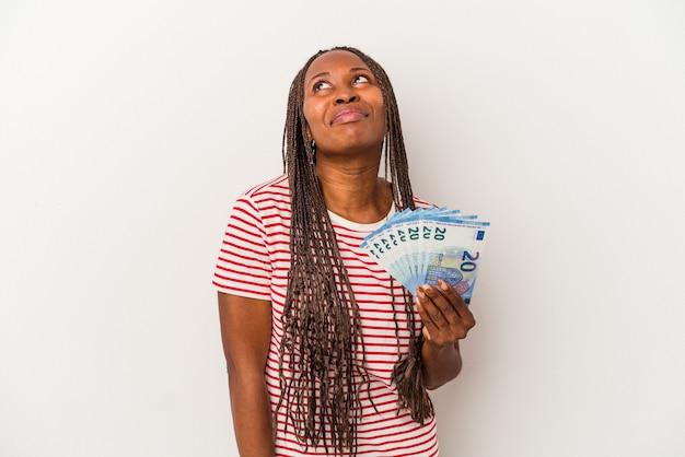 目標と目的を達成することを夢見て白い背景で隔離の紙幣を保持している若いアフリカ系アメリカ人女性