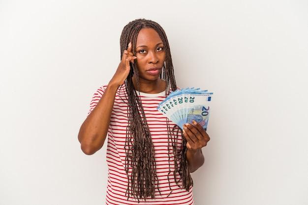指で寺院を指して、白い背景に分離された紙幣を保持している若いアフリカ系アメリカ人の女性は、タスクに焦点を当てて考えています。