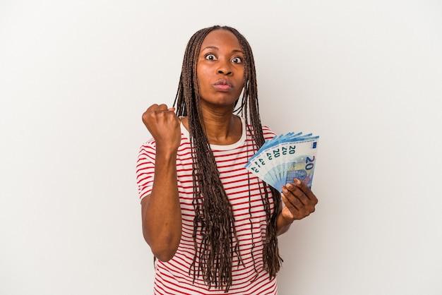 카메라에 주먹을 보여주는 흰색 배경에 고립 된 지폐를 들고 젊은 아프리카 계 미국인 여자, 공격적인 표정.