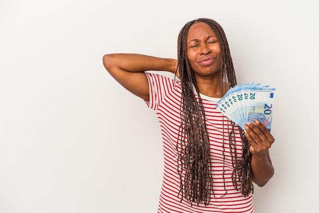 頭の後ろに触れて、考えて、選択をする白い背景に分離された紙幣を保持している若いアフリカ系アメリカ人女性。