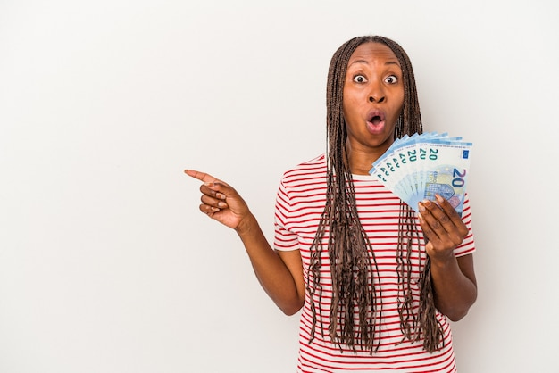 Young african american woman holding banknotes isolated on white background pointing to the side