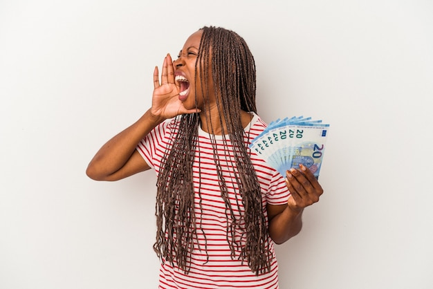 Young african american woman holding banknotes isolated on white background shouting and holding palm near opened mouth.