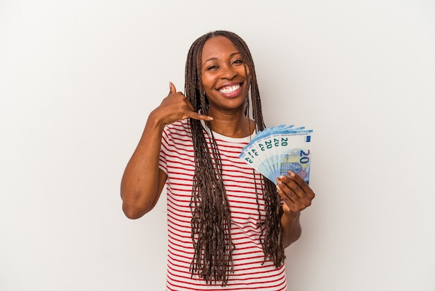 Young african american woman holding banknotes isolated on white background showing a mobile phone call gesture with fingers.