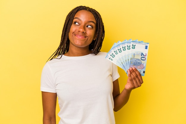Young african american woman holding bills isolated on yellow background  dreaming of achieving goals and purposes