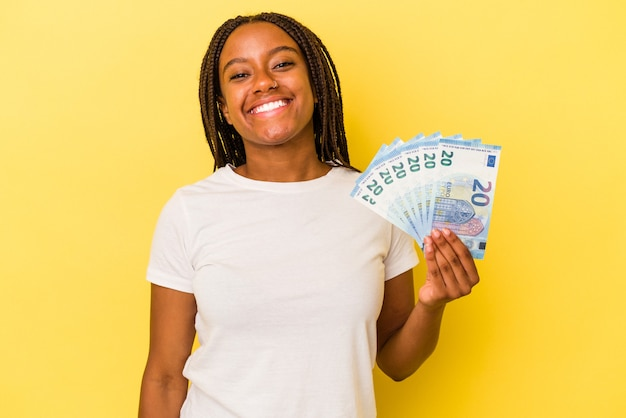 Young african american woman holding bills isolated on yellow background  happy, smiling and cheerful.