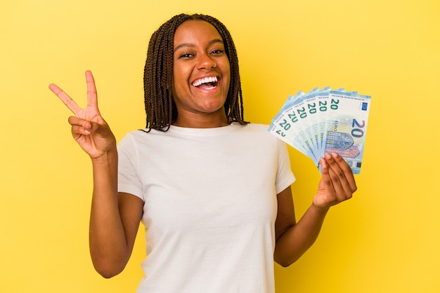 Young african american woman holding bills isolated on yellow background  joyful and carefree showing a peace symbol with fingers.