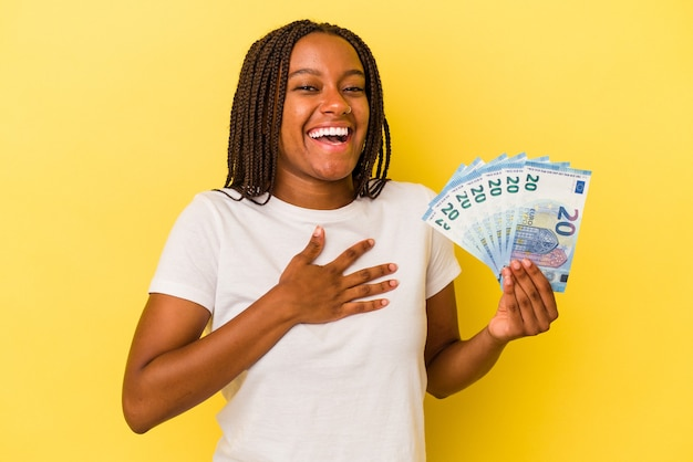 Young african american woman holding bills isolated on yellow background  laughs out loudly keeping hand on chest.