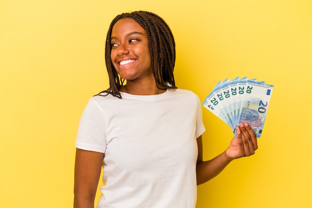 Young african american woman holding bills isolated on yellow background  looks aside smiling, cheerful and pleasant.