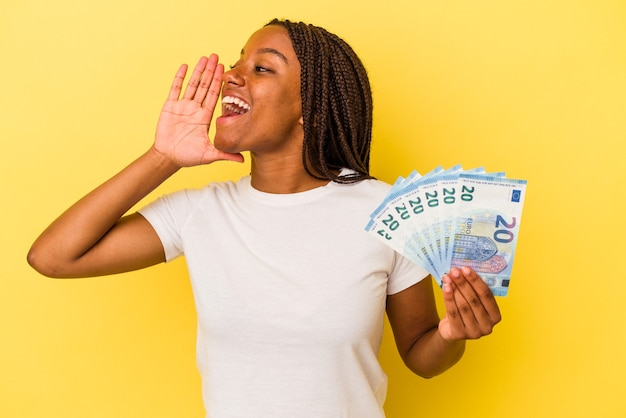 Young african american woman holding bills isolated on yellow background  shouting and holding palm near opened mouth.