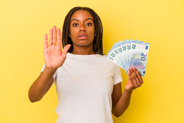 Young african american woman holding bills isolated on yellow background  standing with outstretched hand showing stop sign, preventing you.
