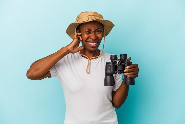 手で耳を覆う青い背景に分離された双眼鏡を保持している若いアフリカ系アメリカ人女性。