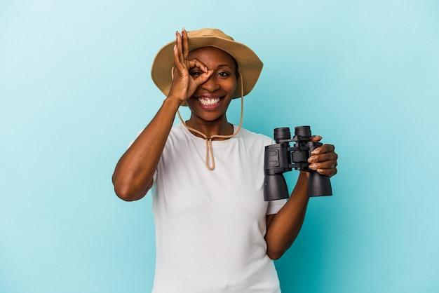 青い背景に分離された双眼鏡を持っている若いアフリカ系アメリカ人の女性は、目に大丈夫なジェスチャーを維持して興奮しています。