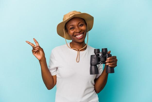 青い背景に分離された双眼鏡を持っている若いアフリカ系アメリカ人の女性は、指で平和のシンボルを示して楽しくてのんきです。